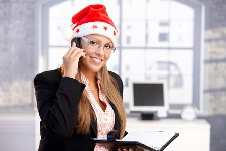 pretty female wearing santa hat, holding organiser, using mobile, smiling in office.� Stock Photo - 10663555
