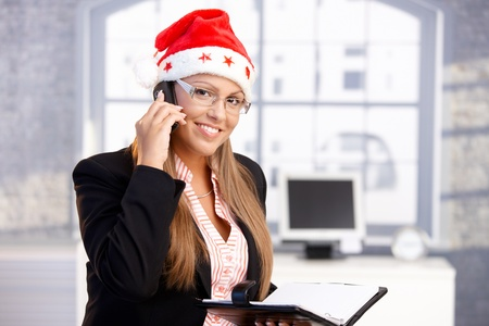 pretty female wearing santa hat, holding organiser, using mobile, smiling in office.� photo