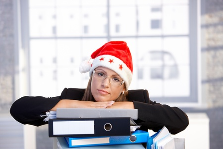 young woman in santa hat sitting in office leaning on folders, having trouble.� photo
