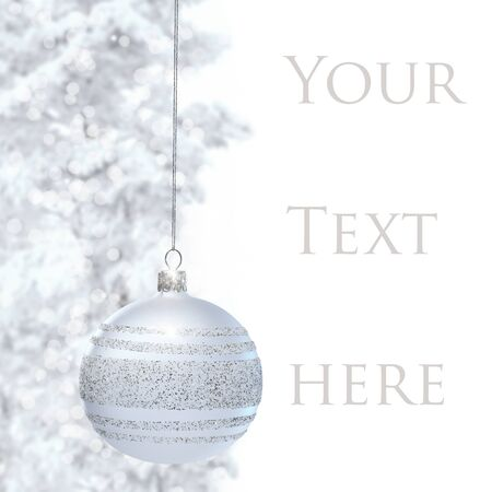 silver balls: Postcard with Christmas bauble and snowy pine. Space for text on right.�