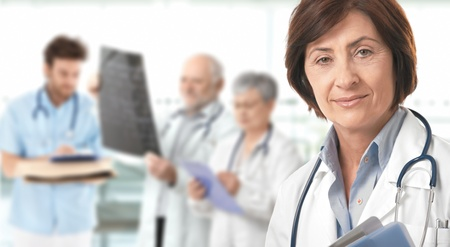 white color worker: Portrait of senior female doctor looking at camera, medical team working in background.�