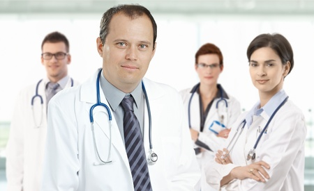 clinical staff: Prtrait of mid-adult doctor leading medical team, smiling.�
