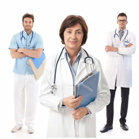 Portrait of experienced female doctor smiling, young male doctors standing behind.� photo