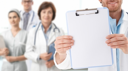smock: Closeup of blank clipboard held by doctor, medical team standing in background.� Stock Photo