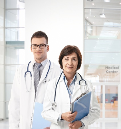 consultant physicians: Portrait of confident doctors in medical center, looking at camera.�