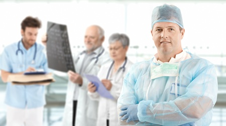 image consultant: Portrait of middle aged male surgeon looking at camera, medical team working in background.