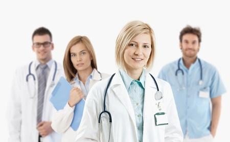 grupo de doctores: Equipo de m�dicos j�venes sonriendo a la c�mara, aislado en blanco. Foto de archivo