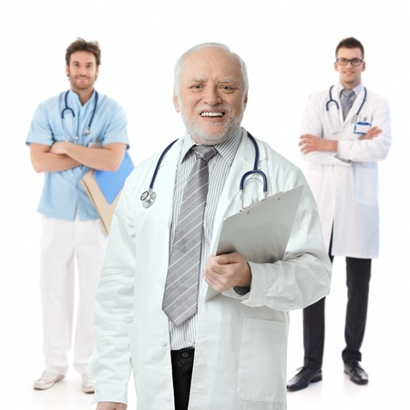 white coats: Three male doctors standing on white background, portrait. Stock Photo