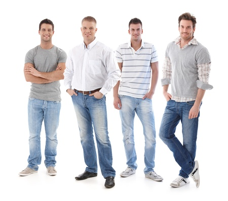 men standing: Full-length portrait of group of young men wearing jeans, looking at camera, smiling.