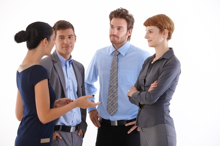 black lady talking: Young businesspeople standing, talking, smiling.