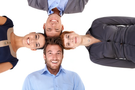 businessteam: Happy businessteam putting heads together, smiling, looking at camera, view from below.