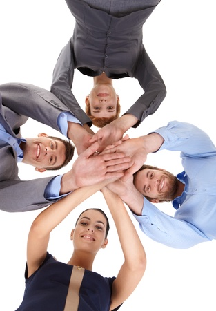 Young businesspeople putting hands together, smiling, looking at camera, view from below. photo