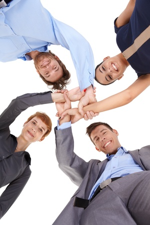 linking: Young businesspeople linking hands, smiling, looking at camera, view from below. Stock Photo