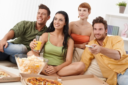 Smiling young companionship watching tv together, having pizza and chips. Stock Photo
