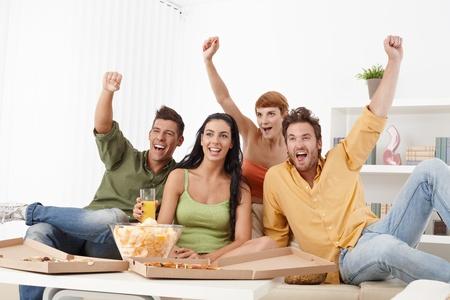 personas viendo tv: J�venes aficionados al f�tbol sentado en casa en jittering sof�, gritando. Foto de archivo