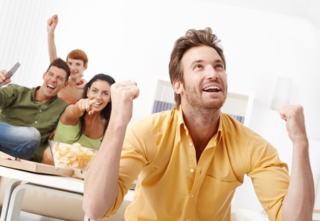 ver tv: Jóvenes amigos viendo el fútbol en la tele en casa, trepidación.