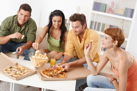 vibrant colors fun: Giovani amici avendo festa a casa, mangiare pizza e patatine, sorridendo.