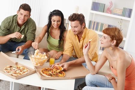 Jonge vrienden met feestje thuis, het eten van pizza en chips, glimlachend. Stockfoto