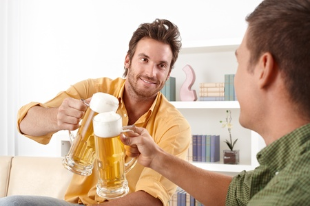 2 persons: Handsome friends clinking with beer glass, smiling. Stock Photo