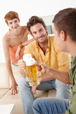 Happy young people having party, drinking beer. photo