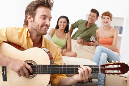 others: Young happy friends having party, one playing guitar, the others listening.