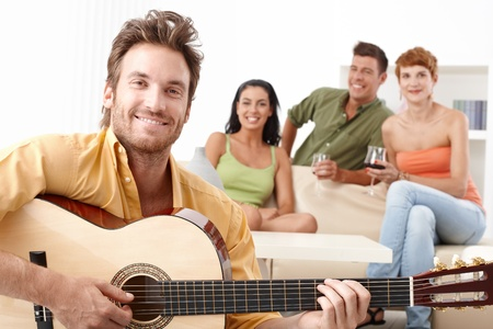 room mate: Happy friends having fun together, playing guitar, smiling.
