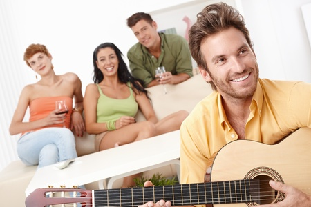 Young friends having party at home, playing guitar, having fun, smiling. photo