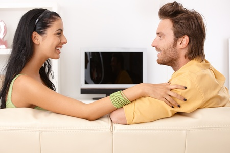 Happy couple chatting on sofa, side view. photo