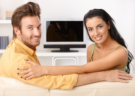 Beautiful young couple sitting on sofa, smiling, looking at camera. Stock Photo - 11157035