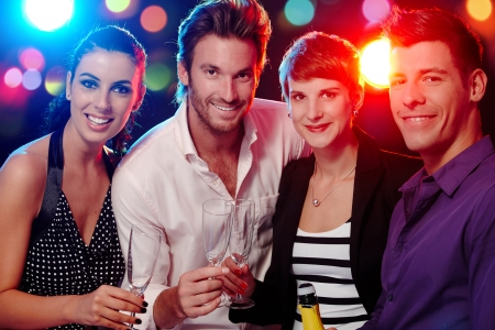 friends at bar: Happy companionship drinking, smiling in discotheque.