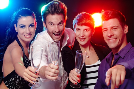 have: Attractive young people having fun in nightclub, smiling, drinking champagne.