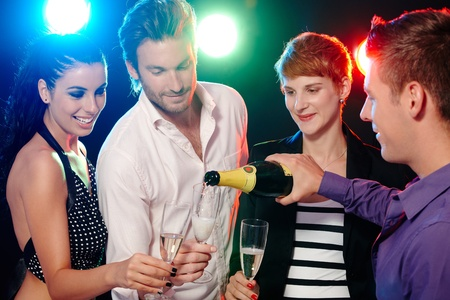 Young friends having fun in disco bar, drinking champagne. photo
