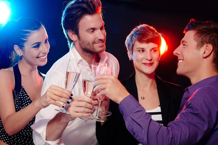 companions: Happy young people clinking with champagne in nightclub.