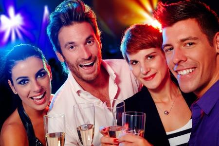 socializando: Atractivos a los jóvenes sonriendo feliz en el club nocturno.