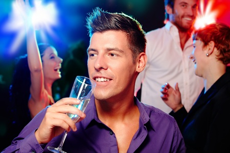 dancing club: Young man drinking champagne at a party, people dancing at background. Stock Photo