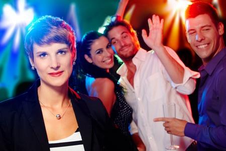 socializando: Mujer joven que mira de afuera en una fiesta, los amigos que se divierten. Foto de archivo