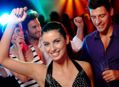 gente bailando: Compañía joven y feliz que se divierte en pista de baile. Foto de archivo