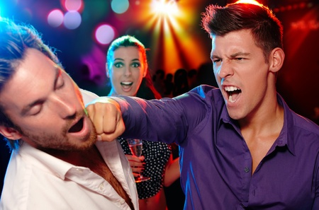 cheating woman: One man hitting another on the face in nightclub, woman watching from background.