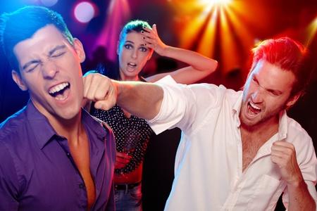 Dos jóvenes bopping en la discoteca para una mujer, que está con cara de preocupación en el fondo.