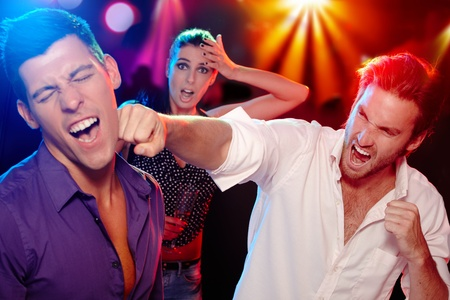 Two young men bopping in the nightclub for a woman, who is looking worried at background. photo