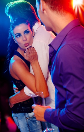 cheating woman: Attractive woman flirting with man in nightclub, while dancing with another. Stock Photo