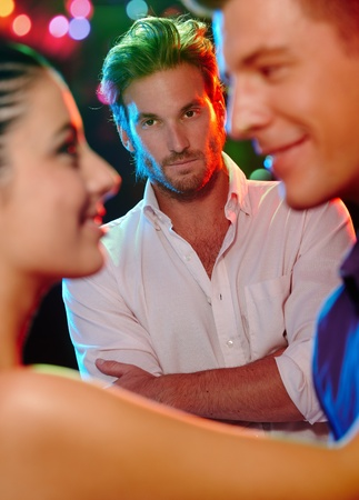 Jealous man looking at dancing couple, flirting girlfriend in nightclub. photo