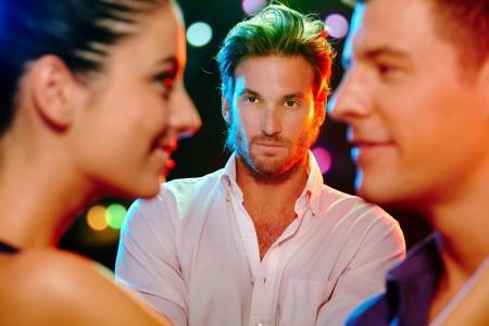 celos: Apuesto hombre celoso viendo coquetear pareja en pista de baile.