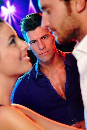 celos: Hombre celoso enojado mirando pareja de baile joven en una discoteca.