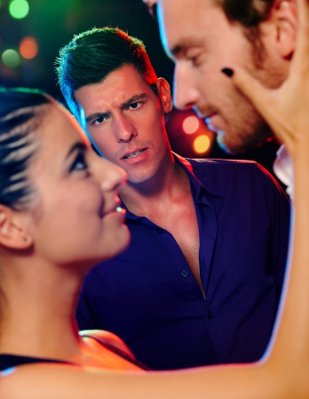 cheating woman: Desperate jealous man looking at flirting couple in discotheque.