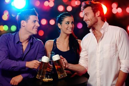 socializando: Felices los j�venes tintineo de vasos en una fiesta con una sonrisa.