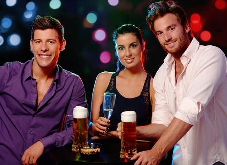 socializando: Atractivos a los j�venes sonriendo, bebiendo en un club nocturno.