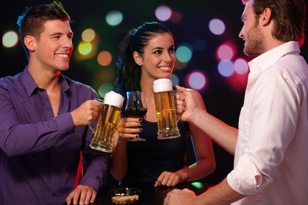 beer drinking: Happy companionship having fun in nightclub, clinking glasses, smiling. Stock Photo
