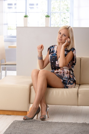 Pretty blond woman wearing mini dress and high heels sitting on living room sofa, using mobile phone. Stock Photo - 11157738