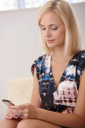 Pretty blonde woman texting on mobile phone at home, smiling. photo